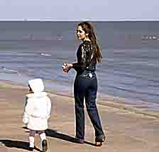 """Young woman with child during winter stroll on seawall sidewalk"""